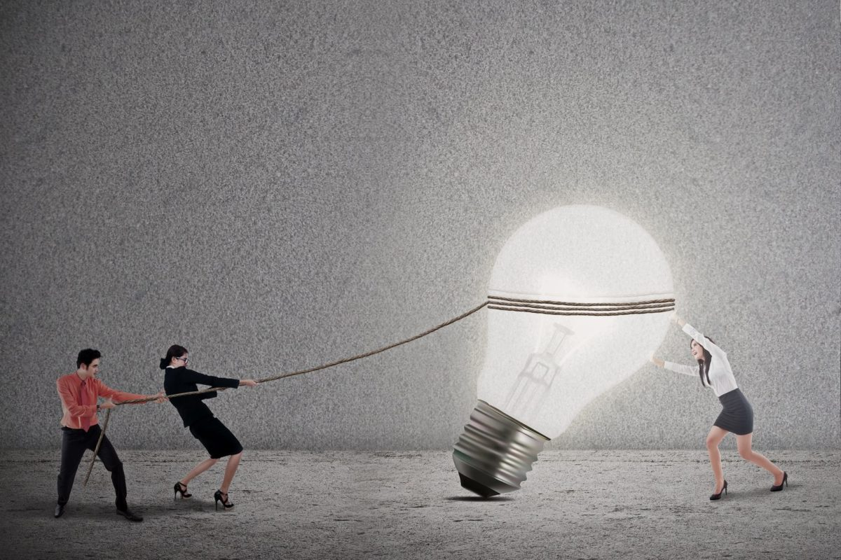 18713777 - business teamwork is pulling a bright light bulb on grey background